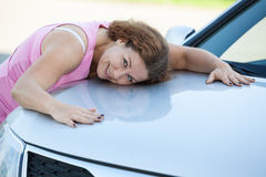 Happy Caucasian woman laying on new vehicle bonnet Royalty Free Stock Image