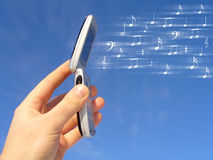 Happy Cellphone Ring-tones. A hand holds up a modern cellphone while musical notes fly through the air symbolizing happy cellphone ring-tones Stock Photo