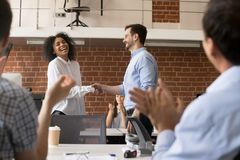 Happy ceo team congratulating successful african worker with job. Happy ceo and team congratulating successful african american worker by shaking clapping hands royalty free stock images
