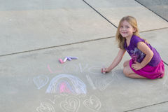 Happy Chalk. A smiling little girl drawing a design on the sidewalk with chalk. Room at the top for copy text Stock Images