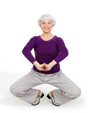Happy charming beautiful elderly woman doing exercises while working out playing sports Stock Image