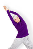 Happy charming beautiful elderly woman doing exercises while working out playing sports. Happy charming beautiful elderly women doing exercises while working stock images