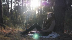 Happy charming woman drinking coffee sitting on plaid outside. Beautiful brunette female in cozy sweater and warm scarf nostalgic. And relaxing in fall forest stock footage