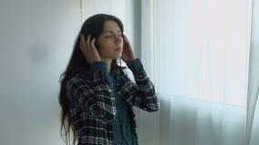 Joyful girl in headphones listening to music at home stock video