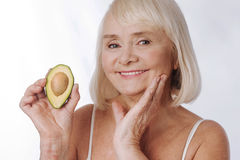 Happy charming woman standing against white background with avocado Stock Images