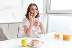 Happy charming woman in white tshirt speaking on mobile phone wh. Ile holding spoon and sitting at the kitchen table Royalty Free Stock Image