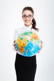 Happy charming young businesswoman giving you an earth globe Stock Image