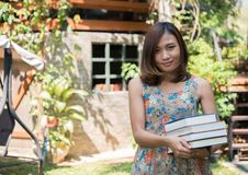 Happy charming young woman standing and holding notebooks at home garden. Education concept. stock image