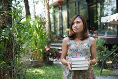 Happy charming young woman standing and holding notebooks at home garden. Education concept. royalty free stock photos