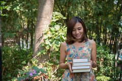 Happy charming young woman standing and holding notebooks at home garden. Education concept. stock photography