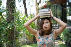 Happy charming young woman standing and holding notebooks at home garden. Education concept. stock photos