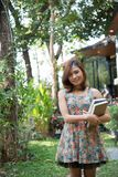 Happy charming young woman standing and holding notebooks at home garden. Education concept. stock photo