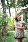 Happy charming young woman standing and holding notebooks at home garden. Education concept. royalty free stock image