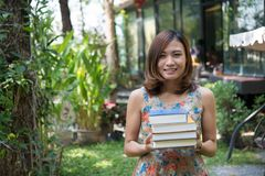 Happy charming young woman standing and holding notebooks at home garden. Education concept. royalty free stock images