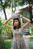 Happy charming young woman standing and holding notebooks at home garden. Education concept. royalty free stock photography