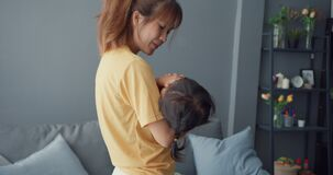 Happy cheerful Asia family mom holding toddler girl cry in arms and comfort care walking in living room at house. Spending time