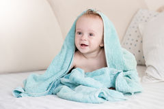 Happy cheerful baby boy sitting on bed under blanket Royalty Free Stock Photos