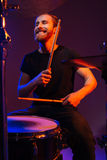 Happy cheerful bearded man drummer playing on kit with sticks Royalty Free Stock Photography