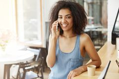 Happy cheerful beautiful african girl smiling looking at camera speaking on phone sitting in cafe. Copy space Royalty Free Stock Photos