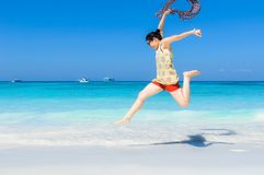 Happy and Cheerful beautiful Asian woman enjoy jumping on a whit. E sand beach holding the blowing scarf with blue sky and blue sea as a background Stock Photos