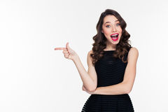 Happy cheerful beautiful young female with retro hairstyle pointing away Royalty Free Stock Images