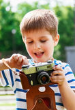 Happy cheerful boy with a camera, the baby photographed outdoors Royalty Free Stock Photography