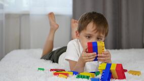 Happy cheerful boy playing with coloured blocks while lying on the bed. A child builds from meccano. stock video footage