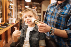 Happy cheerful boy showing the OK gesture. Everything is fine. Happy cheerful positive boy showing the OK gesture and smiling while having his first shaving Royalty Free Stock Image