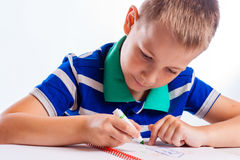 Happy cheerful child drawing with brush in album using a lot of painting tools. Royalty Free Stock Photography