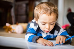 Happy cheerful child drawing at home. Creativity concept Stock Photography