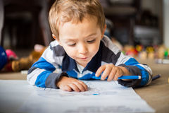 Happy cheerful child drawing at home. Creativity concept Stock Images