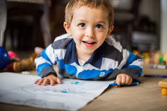 Happy cheerful child drawing at home. Creativity concept. Royalty Free Stock Images