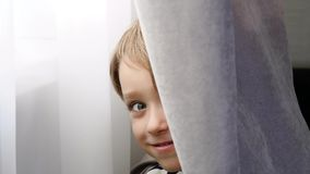 Happy cheerful child playing hide and seek in the room. Playing hide and seek, peek a boo. stock footage