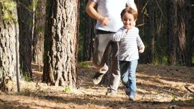 A happy cheerful child runs among the trees in a forest or Park. A father plays with his son in the open air, catching
