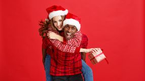 Happy couple black man and caucasian woman in christmas hats on. Happy cheerful couple black men and caucasian women in christmas hats on red background royalty free stock photography