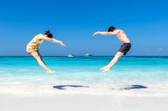 The happy Cheerful couple enjoys relaxing and jumping at white s. And beach with blue sky and blue sea background Royalty Free Stock Photography