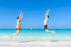 The happy Cheerful couple enjoys relaxing and jumping at white s. And beach with blue sky and blue sea background Royalty Free Stock Photo