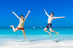 The happy Cheerful couple enjoys relaxing and jumping at white s. And beach with blue sky and blue sea background Stock Photo