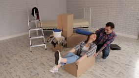 Happy cheerful couple having fun in new apartment. Happy cheerful couple having fun in a new apartment. Happy girl sitting in a cardboard box, the couple moved stock video footage