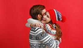 Happy couple man and woman in christmas hats on red backgrou stock photos