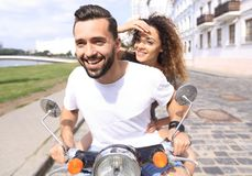 Happy cheerful couple riding vintage scooter outdoors. Royalty Free Stock Photo