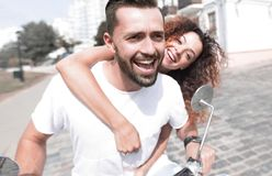 Happy cheerful couple riding vintage scooter outdoors. Cool men and beautiful girl riding on  scooter with  expression Stock Image