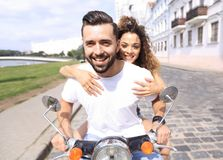 Happy cheerful couple riding vintage scooter outdoors. Royalty Free Stock Images