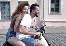 Happy cheerful couple riding vintage scooter outdoors. Royalty Free Stock Image