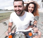 Happy cheerful couple riding vintage scooter outdoors. Stock Photos
