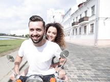 Happy cheerful couple riding vintage scooter outdoors. Cool men and beautiful girl riding on  scooter with  expression Royalty Free Stock Photography