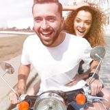 Happy cheerful couple riding vintage scooter outdoors. Cool men and beautiful girl riding on  scooter with  expression Royalty Free Stock Images