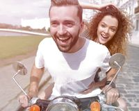 Happy cheerful couple riding vintage scooter outdoors. Cool men and beautiful girl riding on  scooter with  expression Royalty Free Stock Photo