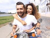 Happy cheerful couple riding vintage scooter outdoors. Cool men and beautiful girl riding on  scooter with  expression Stock Images