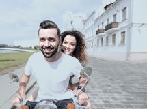 Happy cheerful couple riding vintage scooter outdoors. Cool men and beautiful girl riding on  scooter with  expression Stock Photos